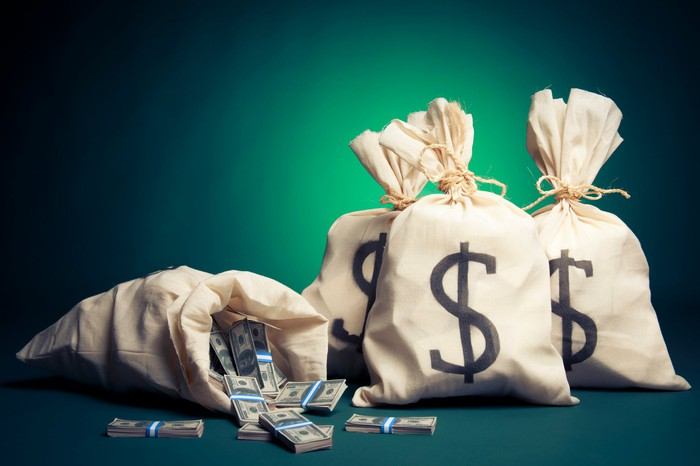 Four canvas bags are shown, marked with dollar signs. One is open and on its side, with cash spilling out.