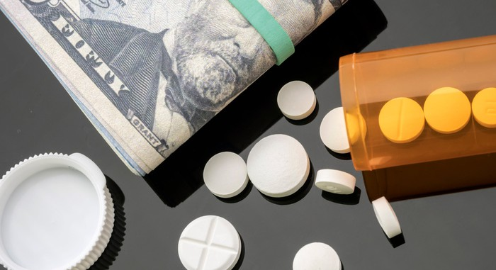 A folded wad of U.S. banknotes next to an overturned bottle of some prescription pills.