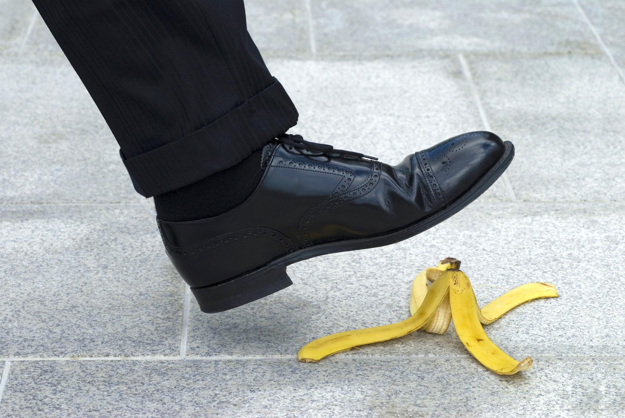 The foot of a man in a suit about to step on a banana peel.