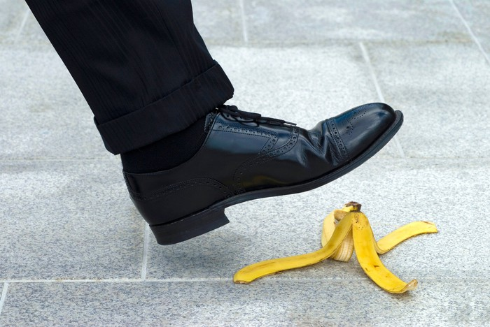 The foot of a man in a suit about to step on a banana peel.