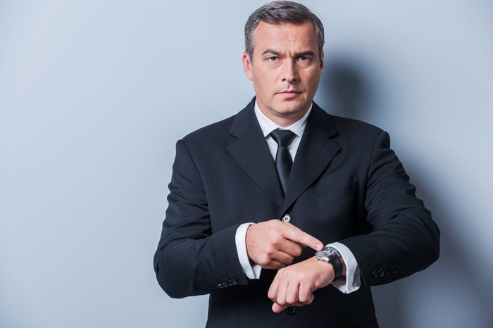 A businessman in a suit pointing at his watch.