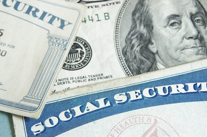 Two Social Security cards lying atop a hundred-dollar bill.