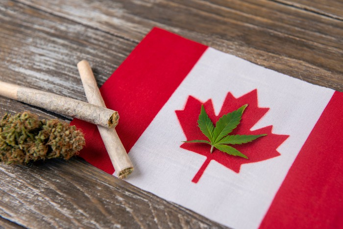 A cannabis leaf lying down within the outline of a red maple leaf in the Canadian flag, with two pre-rolled joints and a cannabis bud to the left of the flag.