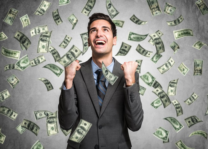 A businessman stands in a shower of hundred dollar bills.