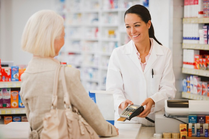 Woman in white coat in a pharmacy holding credit card reader out to woman across the counter.