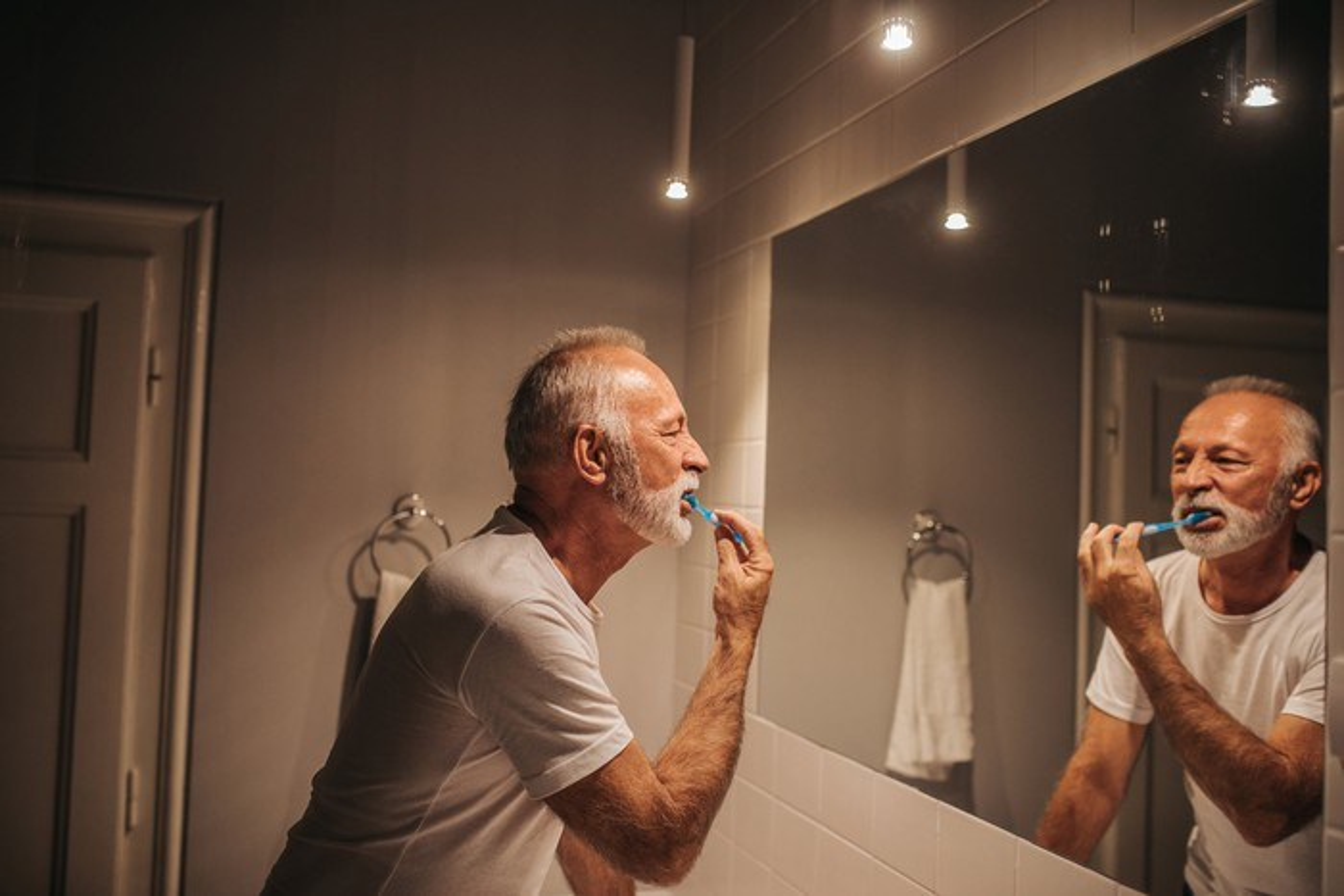 A senior man looks in the bathroom mirror as he brushes his teeth.