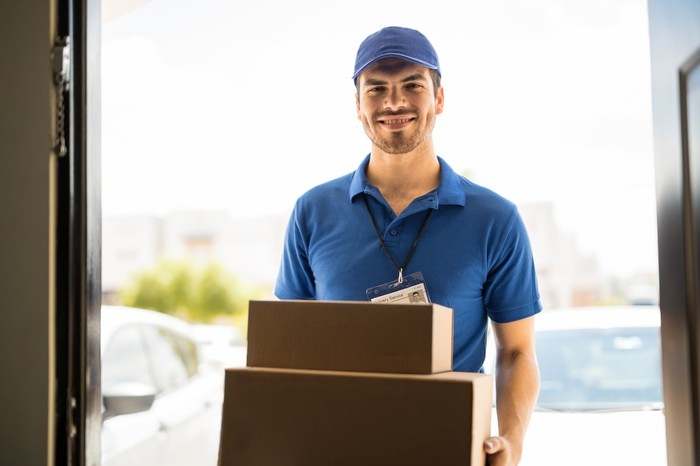 A delivery man smiles and holds packages in a doorway.