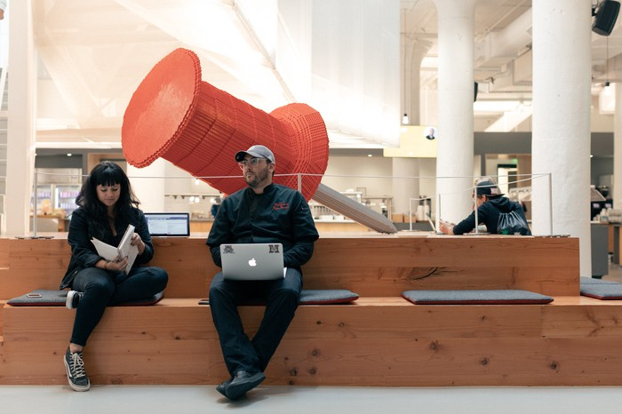 Two Pinterest employees sitting in front of a giant pin.
