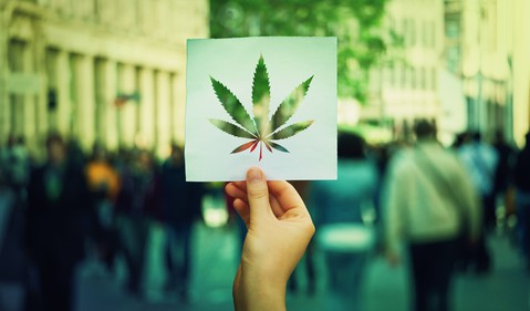 Hand holding up paper sheet with marijuana leaf with crowded street