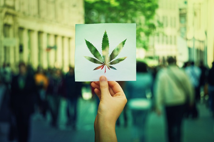A hand holding up paper sheet with a marijuana leaf cut out of it and a crowded street in the background.