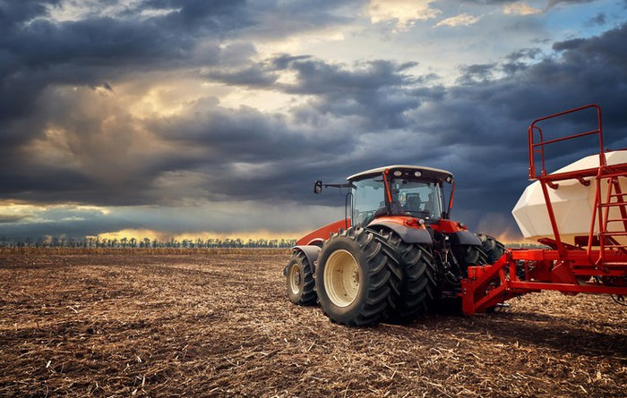 A red tractor in a field with dark clouds overhead.