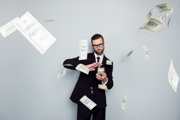 A man in a suit tossing $100 bills in the air.