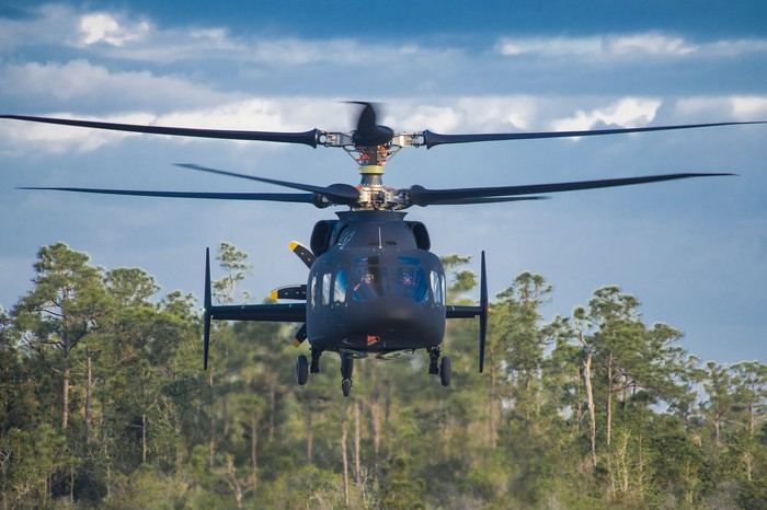 The Defiant hovers over an airfield with pine trees in the background.