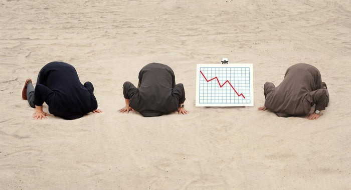 Three businessmen sticking their heads in the sand as a chart next to them shows a red down arrow.