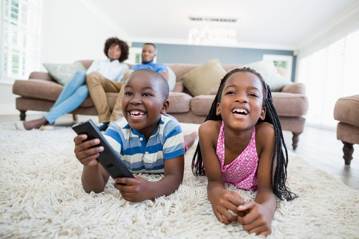 Two smiling children watching television while lying on a rug, with their parents seated on a couch in the background.