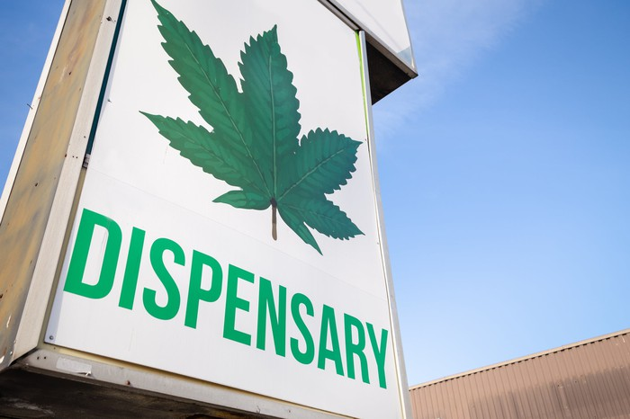 A cannabis dispensary storefront sign that depicts a large cannabis leaf with the word dispensary underneath it.