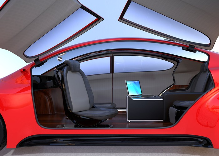 Wing doors on one side of a red sports car raised showing an interior that has seats facing each other and a table with a laptop on it, but no steering wheel -- concept for a self-driving vehicle.