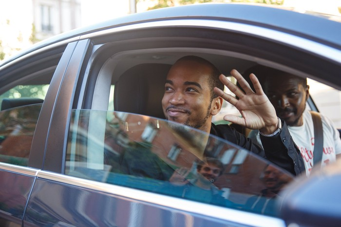 Man waving from car.