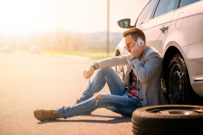 Man sitting against car on the side of the road, talking on a smartphone