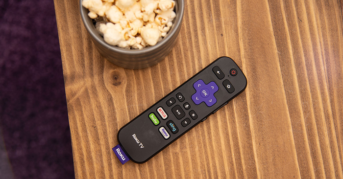 A Roku TV remote on a table next to a bowl of popcorn.