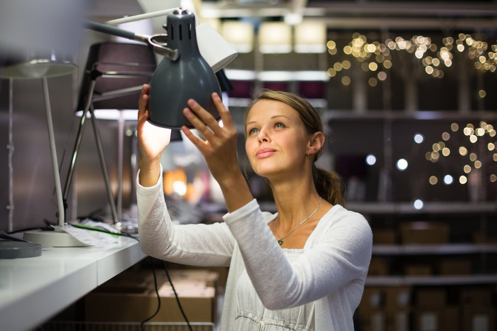A woman checks a lamp at a home goods store.