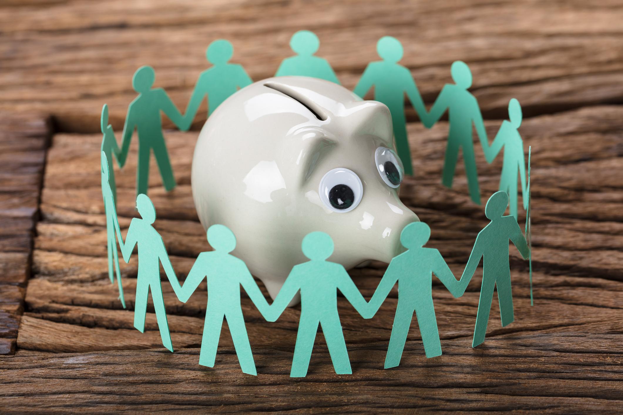 Paper people encircle a piggy bank.