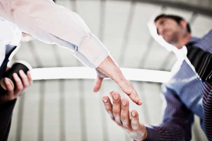 Two businessmen shake hands in a view from underneath.