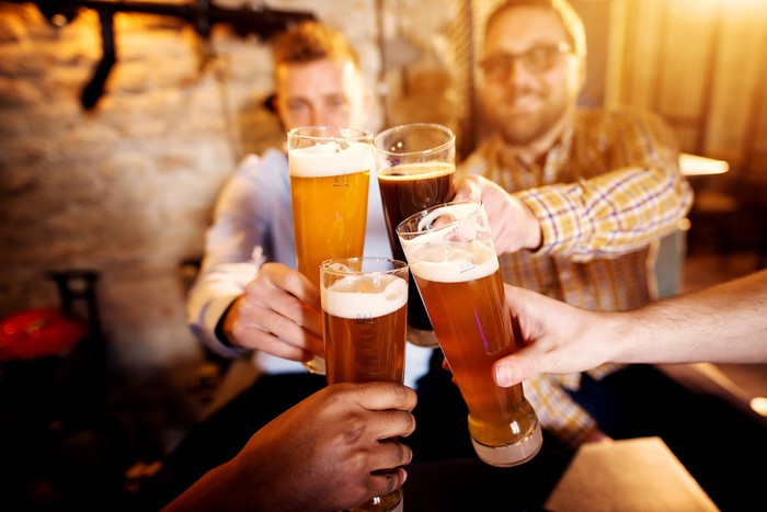 Four friends drinking beer in a bar