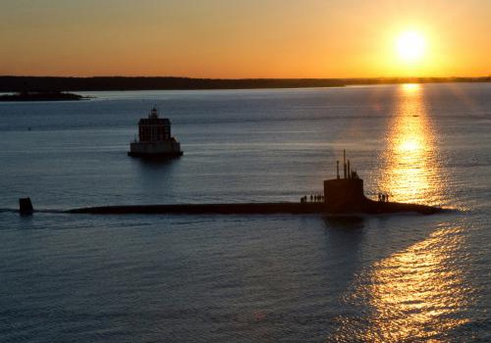 A Virginia-class submarine in front of a sunrise.