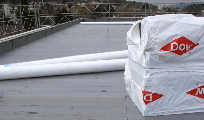Two piles of Dow-wrapped materials on a roof.