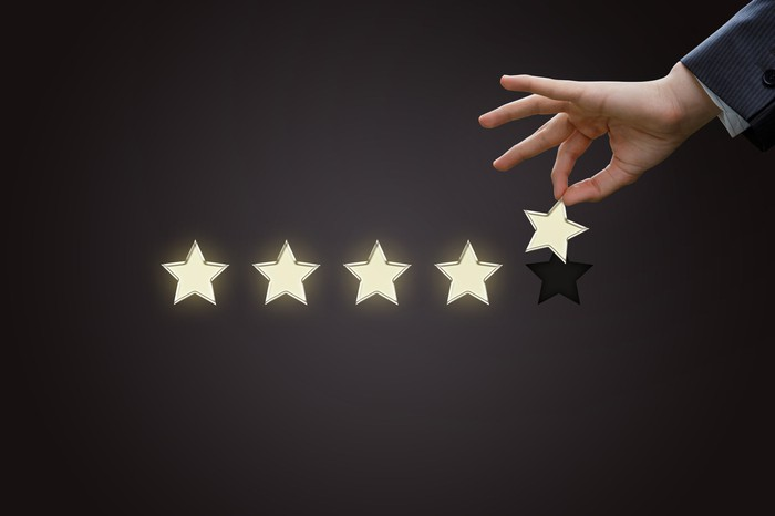 Businessman's hand holding a gold star next to four other stars