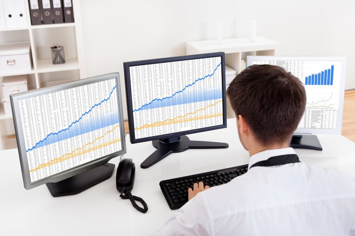 Man looking at three monitors displaying financial data.