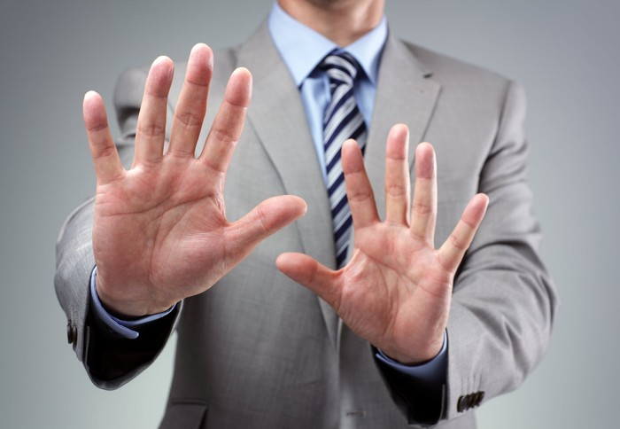 A businessman in a suit putting his hands up as if to say no thanks.