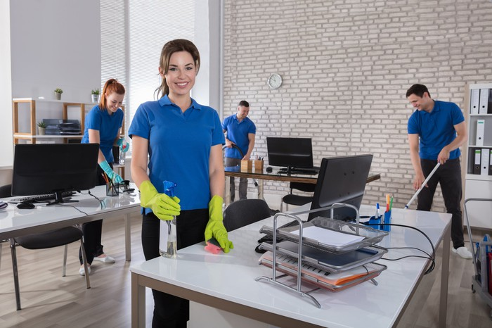 Team of janitors in matching work uniforms cleaning a modern office.