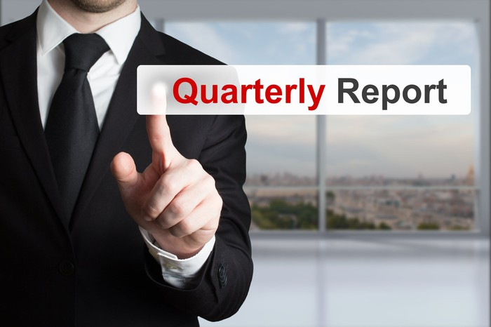 A businessman in a black suit touching the quarterly report icon on a digital screen.