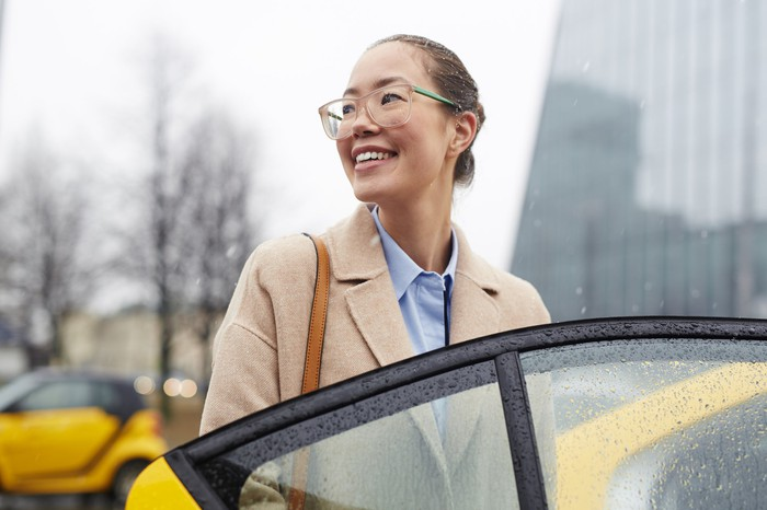 A smiling, bespectacled woman entering a yellow cab.