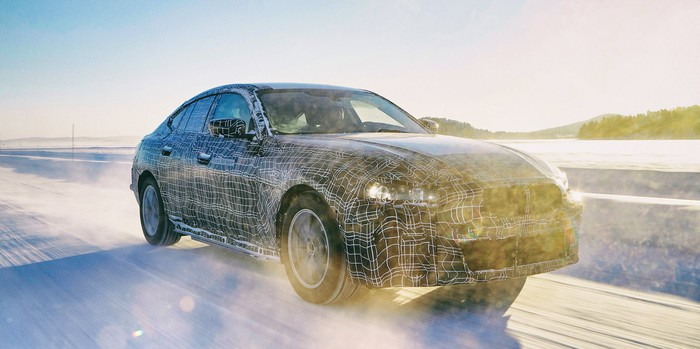 A prototype BMW i4, a midsize electric luxury-sports sedan, driving on snowy proving grounds