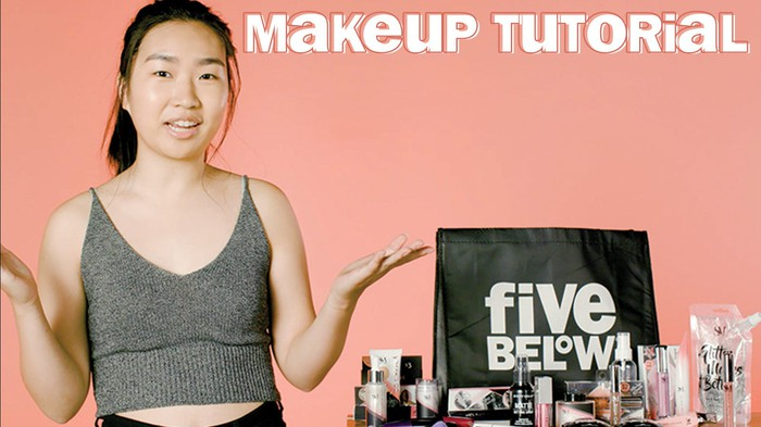 Woman next to a table of makeup products and a Five Below bag.