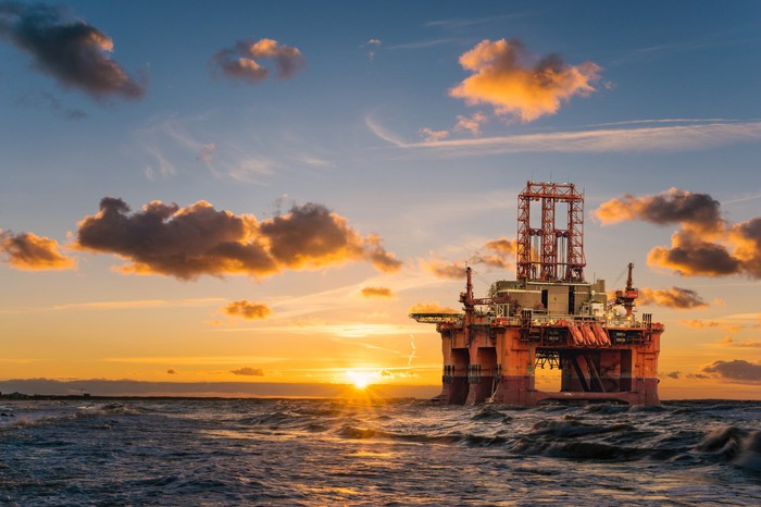 A drilling rig in the water with the sun setting in the background.