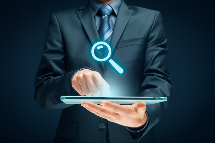A person pointing to a tablet computer with a holographic image of a magnifying glass above it.