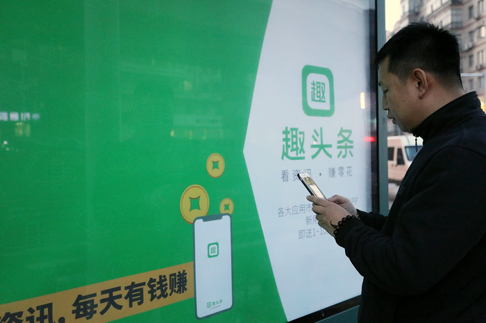An ad for Qutoutiao with someone scanning the mobile code for access.