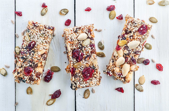Granola bars with dried fruit and nuts on a wood table.