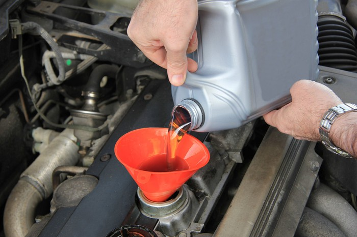 A mechanic topping off engine fluid.