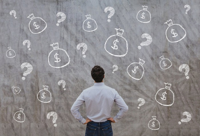 A man staring at a blackboard covered by drawings of money bags and question marks.