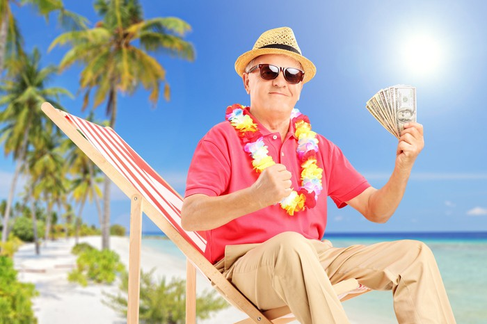 An older man sitting at the beach holding cash.