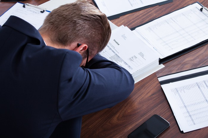A man in business attire puts his head down on a desk covered with documents.