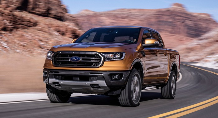 An orange 2019 Ford Ranger, a midsize pickup, shown on a mountain road.