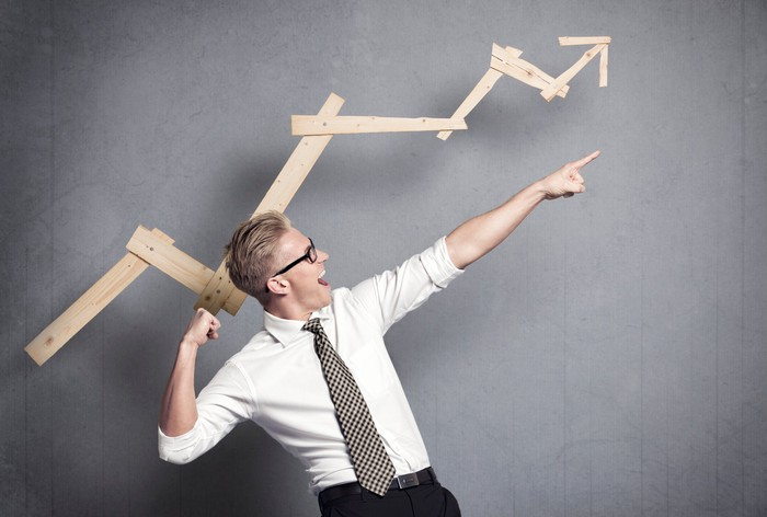 Man in white shirt and spotted tie celebrating in front of a wooden arrow chart indicating gains.