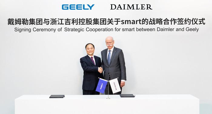 """The two executives are standing before a banner that reads, in English and Chinese, """"Signing Ceremony of Strategic Cooperation for Smart between Daimler and Geely."""""""
