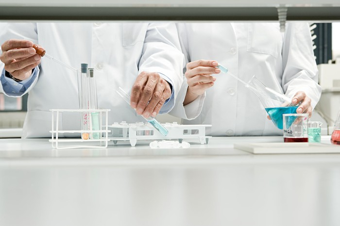 Two people in lab coats in a lab holding test tubes and beakers.
